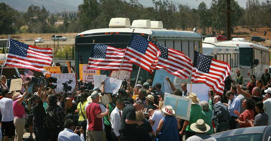 Protesters turn back three buses carrying 140 immigrants as they attempt to enter the Murrieta U.S. Border Patrol station for processing on Tuesday, July 1, 2014, in Murrieta, Calif.  MAGS OUT; MANDATORY CREDIT Photo: DAVID BAUMAN, AP / The Press-Enterprise