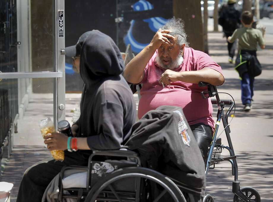 In this file photo a pair of men in wheelchairs waited in front of a small grocery near Jones and Market Streets Wednesday July 2, 2014. Photo: Brant Ward, San Francisco Chronicle