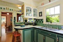 This kitchen in Albany is adorned with colorful tile counters and backsplashes and painted cabinets.