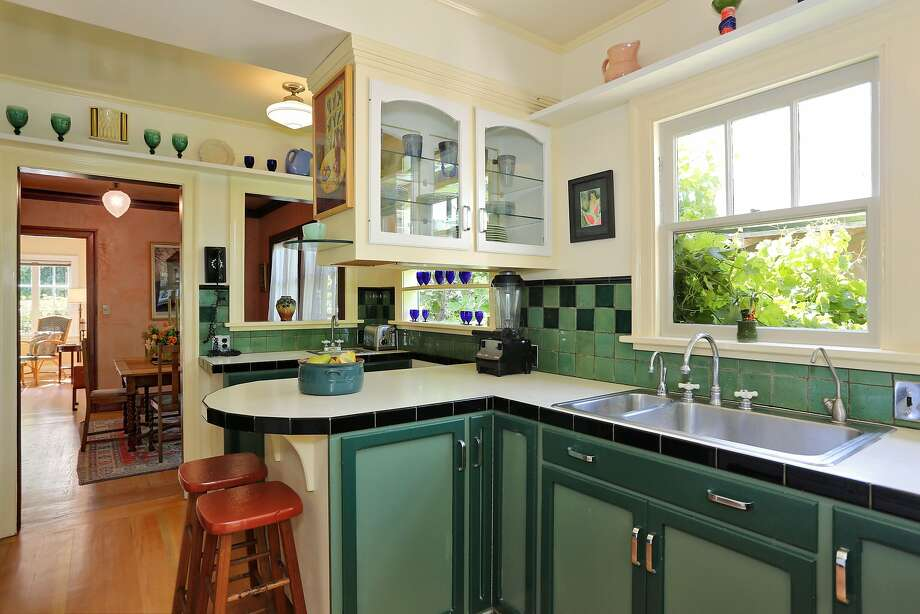 Hardwood floors highlight this kitchen in Albany, which is also adorned with colorful tile counters and backsplashes with painted cabinets. Photo: Liz_Rusby/The Grubb Company