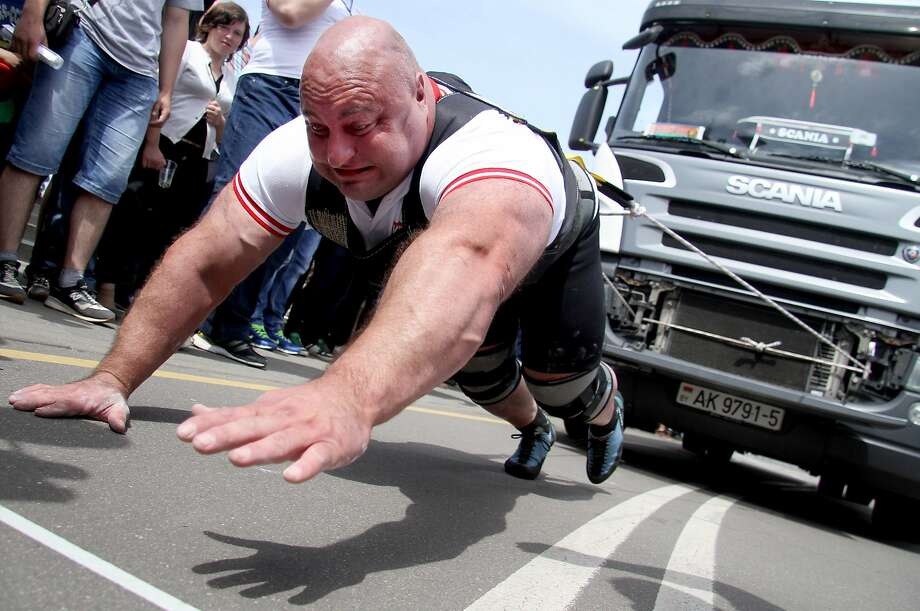 Fireworks, nyet. Truck pull, da! A strong-man contestant strains to move a 15-ton truck during a truck pull 
