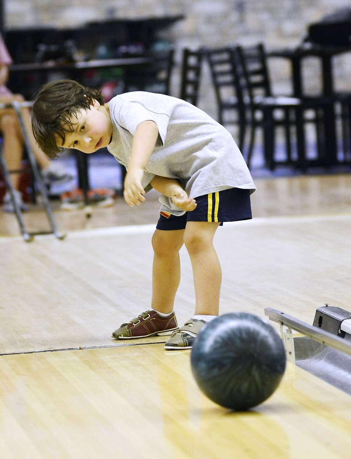 Uh-oh, look at that foot. Lane violation:Three-year-old Parker Umphlett rolls a ball down a lane at the High Point Bowling Center in High Point, N.C.