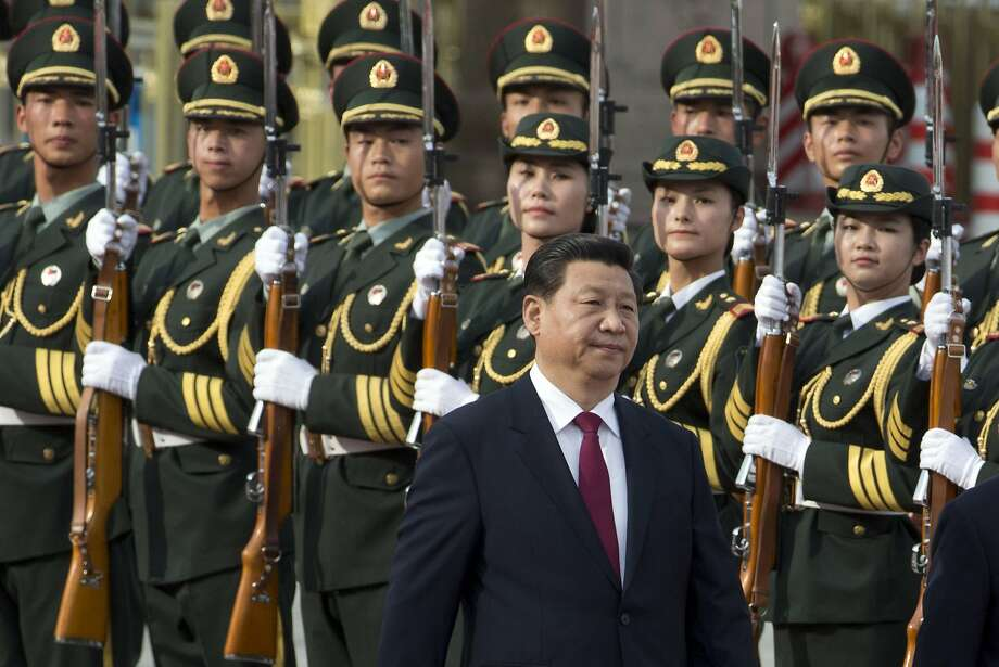 In this photo taken, Friday, June 27, 2014, Chinese President Xi Jinping walks near a guard of honor at a welcome ceremony for Myanmar President Thein Sein in Beijing, China. The ouster of one of China's top military figures reflects Communist Party leader Xi's determination to impose his personal authority far more ambitiously than his recent predecessors. Since being appointed party leader in late 2012, Xi has moved aggressively to make his personal stamp with campaigns against graft and official waste and by waging an offensive against liberal, Western ideas. Party and government officials and managers of state companies have fallen. Advocates for official transparency and a fairer society have been jailed. (AP Photo/Ng Han Guan) Photo: Ng Han Guan, Associated Press