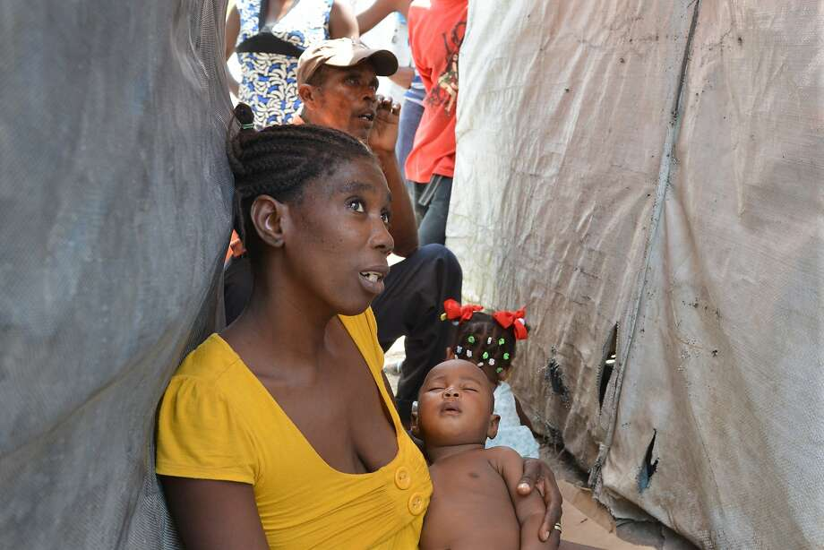 Evelyn Melisma holds her 7-month-old baby outside their tent home in Port-au-Prince, as his fever spikes due to a new mosquito-borne illness. Photo: David McFadden, Associated Press