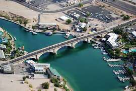FILE - In this June 3, 2009 file photo, provided Courtesy of the Lake Havasu City Convention and Visitors Bureau, shows London Bridge, which spans the Colorado River at Lake Havasu City, Ariz. The London Bridge is not falling down, despite a British tabloid saying that the Lake Havasu City tourist attraction is being bulldozed to make way for drug tourism. Lake Havasu City officials heard about the story in The Sun after a local resident visiting the United Kingdom brought back a copy of the tabloid. They say it was a slap in the face and demanded a retraction and an apology. (AP Photo/Courtesy of the Lake Havasu City Convention and Visitors Bureau)