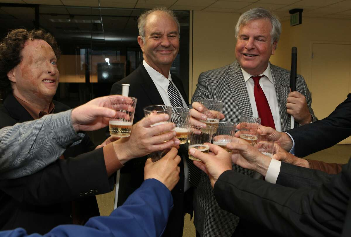 Joshua Miele of Lighthouse for the Blind (left), Ian Paget of Patson Companies (center) join in a toast with Bryan Bashin the Lighthouse's Director and others while celebrating their future office location in San Francisco Calif. on Wednesday, June 25, 2014. The Lighthouse for the Blind has existed in San Francisco for over 100 years and starting next year will occupy the top three floors of 1155 Market St.