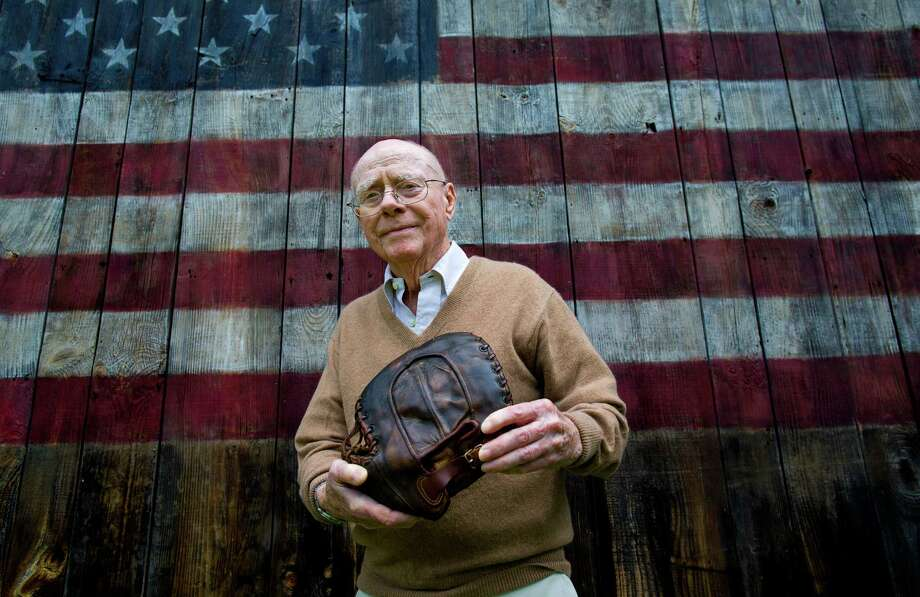 Howard Henderson, who as a boy in New York played catch with baseball legend Lou Gehrig, holds a signed baseball mitt given to him by Gehrig when he was young, near Henderson's Greenwich, Conn., home on Monday June 30, 2014. Gehrig, a Yankee first baseman and a friend of Henderson's songwriter father, visited his home and Henderson visited him when he had ALS. The mitt, that was autographed by Gehrig with a hot instrument, will be auctioned in July, expecting to fetch $200,000 to $300,000. Photo: Craig Ruttle, AP Photo/Craig Ruttle / Associated Press    Greenwich Time contributed