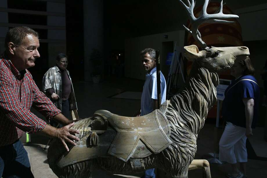 Bob wheels in an early 20th century carousel reindeer to be appraised at the event at the Santa Clara Convention Center. Photo: James Tensuan, The Chronicle