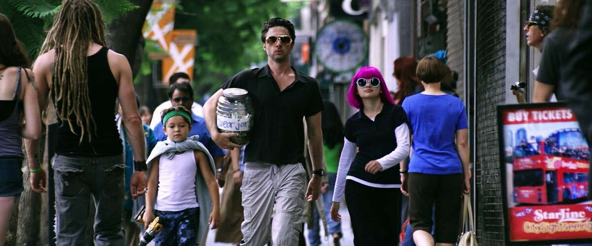 Zach Braff (at center) directs and stars as parent to children portrayed by Pierce Gagnon (at left) and Joey King (at right) in his new comedy WISH I WAS HERE.