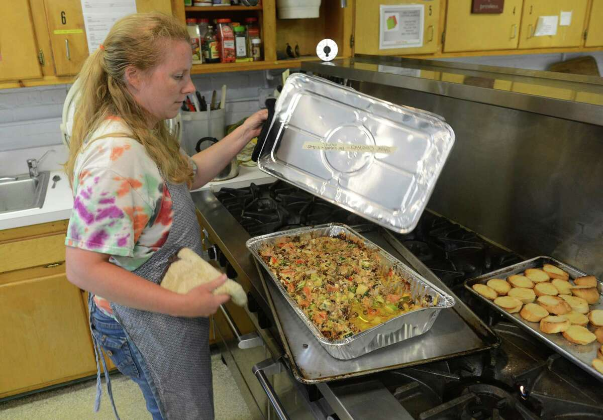 Faith Church volunteer Lindy Carter cooks a casserole in the kitchen of Loaves & Fishes Hospitality House in New Milford, Conn. Thursday, July 3, 2014. The soup kitchen, which provides a hot meal and bagged lunch for more than 20 people daily, is trying to find new space because town officials say they need more room in the town-owned Richmond Community Center.