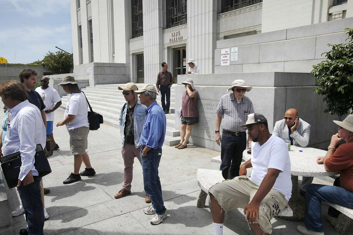 People gather for a daily foreclosure auction, including Robert Kramer, eighth from left, May 1, 2014 at the Alameda courthouse in Oakland, Calif.