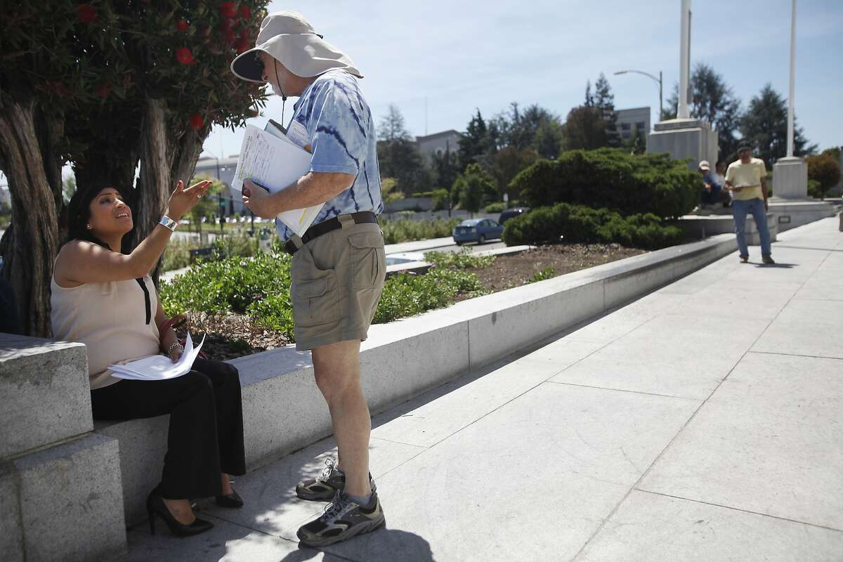 Robert Kramer talks to an employee of his who did not want to be named during a daily foreclosure auction April 29, 2014 at the Alameda courthouse in Oakland, Calif.