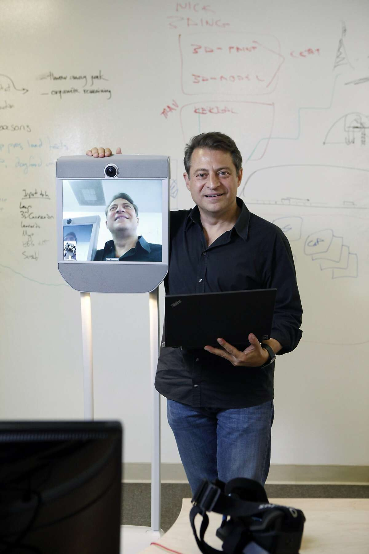 Peter Diamandis holds his laptop as he poses for a portrait next to a Beam telepresence robot at the Singularity University at Moffett Field in Mountain View, CA, Friday May 20, 2014.