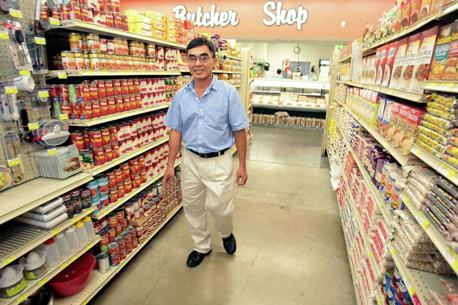 (Center) John Vuong, a Vietnamese immigrant who owns grocery stores in low-income neighborhoods at his supermarket  Pyburn's s in Houston, TX. (Billy Smith/Houston Chronicle) Photo: Billy Smith II / © 2013 Houston Chronicle