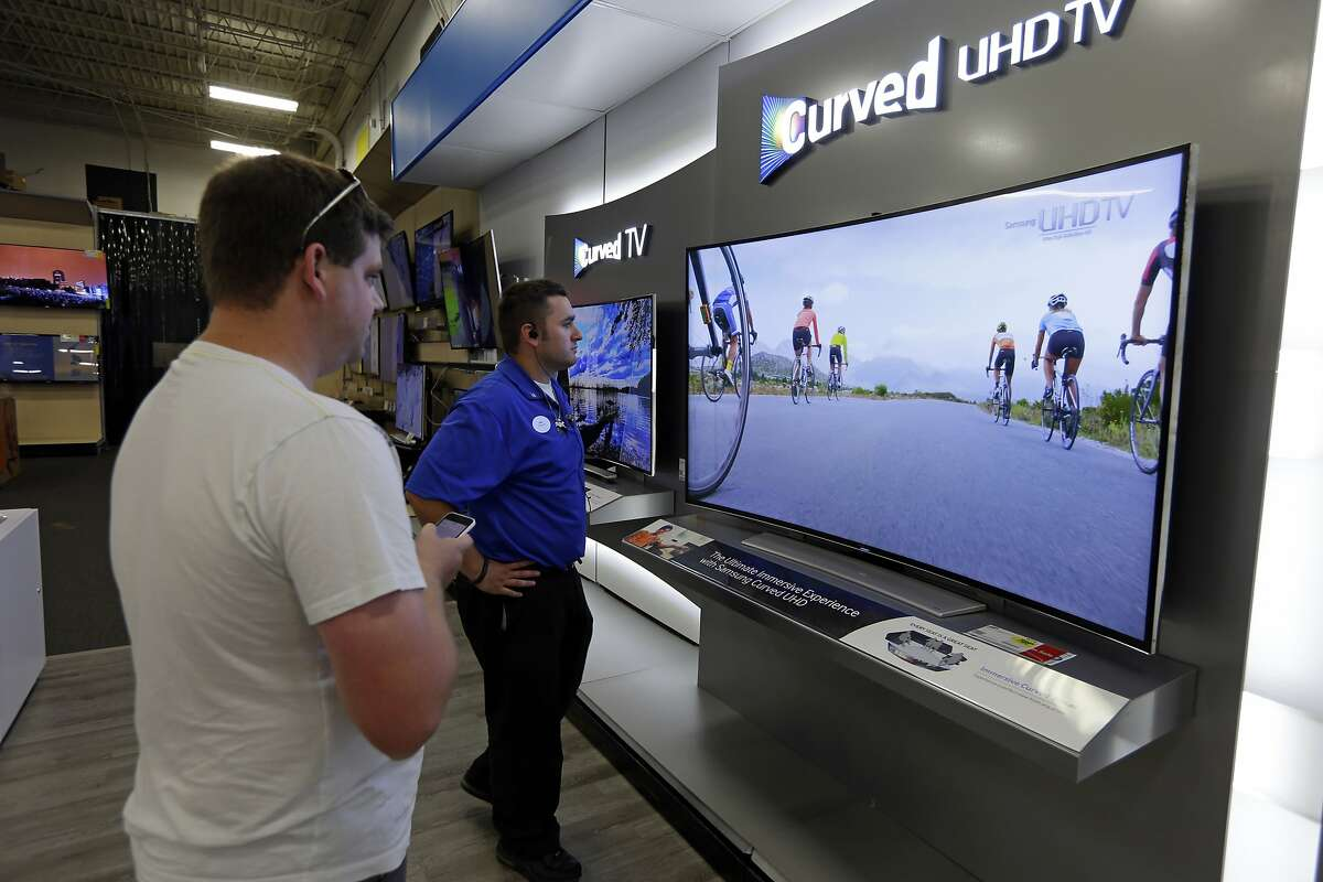 In this Wednesday, June 18, 2014 photo, Jake Willis, center, home theatre supervisor at the Best Buy store in Greenwood, Ind., talks with customer Landon Leichter, of Spencer, Ind., at a display featuring a Samsung 78-inch curved television on display at the store in Greenwood, Ind. The 78-inch television is flanked by 65-inch versions. Americans increasingly are replacing their once-enviable 50-inch TVs with even bigger screens. (AP Photo/Michael Conroy)