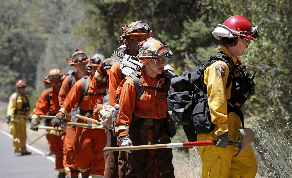 A Department of Corrections fire crew walk along Butts Canyon Road as firefighters continue the battle against the Butts Fire on Thursday July 3, 2014, in Pope Valley, Calif.