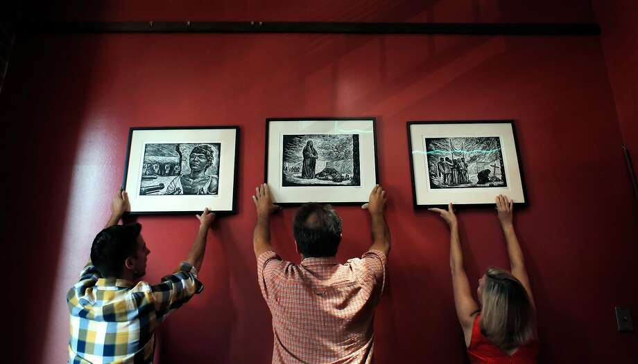 Tyler Paxton, Carl Hall, Kathleen Anderson of Pacific Media Workers Guild look over framed prints by Leopoldo Méndez. Photo: Carlos Avila Gonzalez, The Chronicle