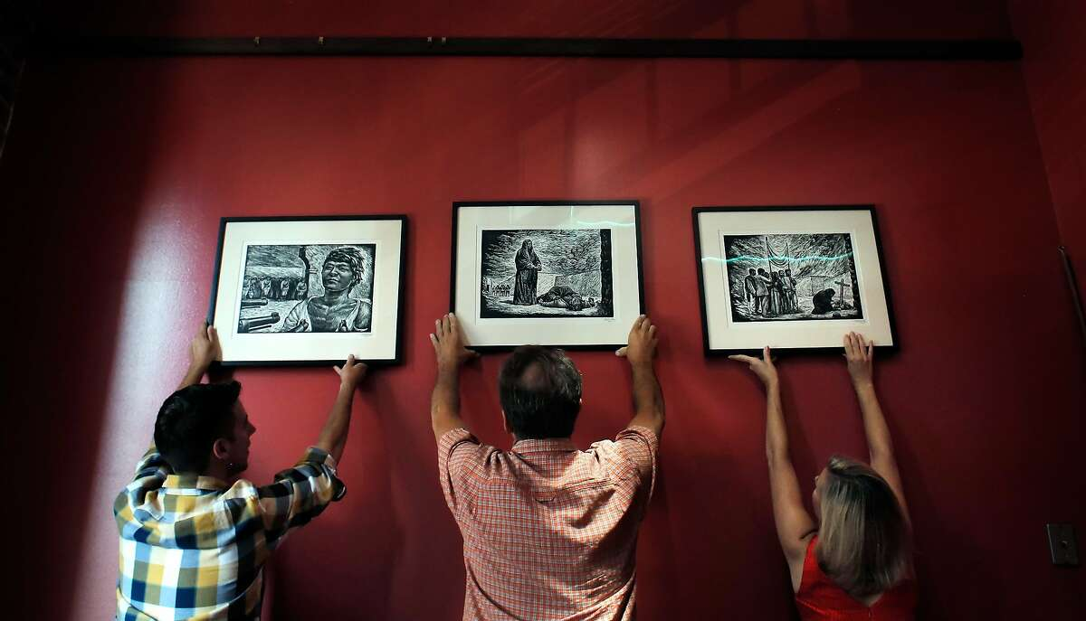 (l-r) Kathleen Anderson, Carl Hall, and Tyler Paxton, of the Pacific Media Workers Guild, look over framed linocut prints by artist Leopoldo Mendez in the guild's office in San Francisco, Calif, on Monday, June 30, 2014. The prints were purchased by a guild member decades ago for about a dollar, and they were recently found to be worth thousands apiece.