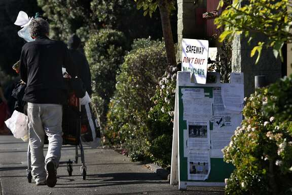 Jimmy Green (left) used the recycling center next to the Market Street Safeway in San Francisco, Calif., for the past 25 years and passes signs in efforts to keep the facility open on Friday, January 10, 2014.  A law suit was filed and protests have recently been held to keep the long time recycling center open.