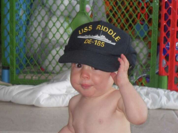 John Everett Marks, age 1, of Roswell, Georgia, proudly wears a Navy hat belonging to his grandfathe