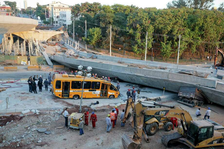 A bus sits damaged next to a bridge after it collapsed in Belo Horizonte, Brazil, Thursday, July 3, 2014. The overpass under construction collapsed Thursday in the Brazilian World Cup host city. The incident took place on a main avenue, the expansion of which was part of the World Cup infrastructure plan but, like most urban mobility projects related to the Cup, was not finished on time for the event. Photo: Victor R. Caivano, Associated Press / AP