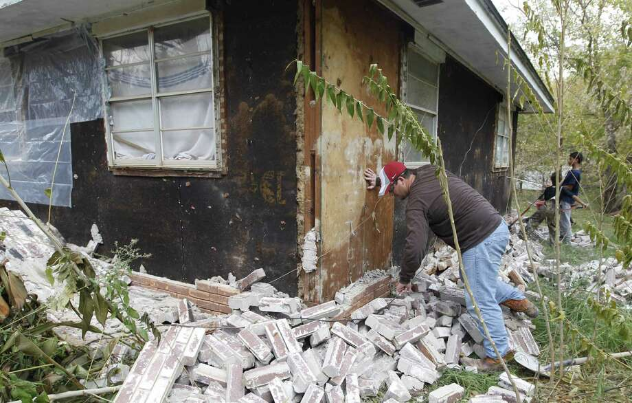 Chad Devereaux examines damage to a home in Sparks, Okla., on Nov. 6, 2011, after two earthquakes hit within 24 hours. A new study says four wells forcing massive amounts of drilling wastewater into the ground are probably causing quakes in Oklahoma. Photo: Associated Press File Photo / AP