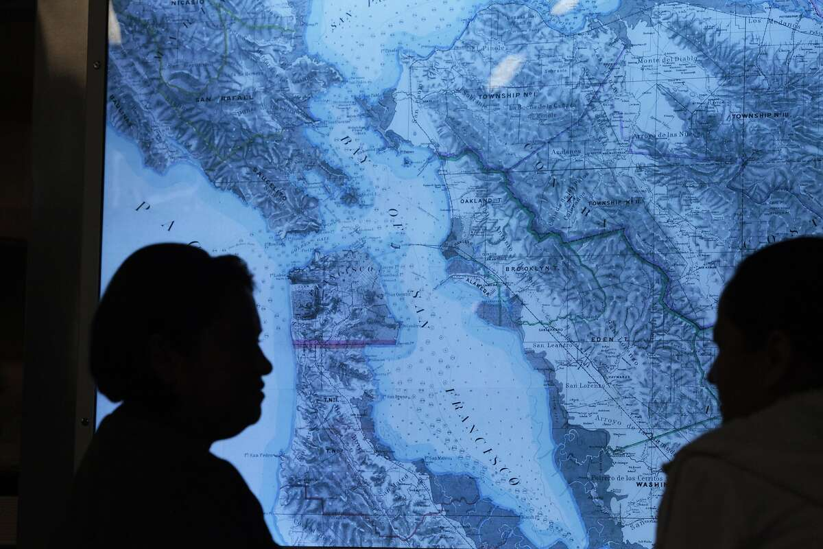 Two women chat in an exhibit of historic maps of San Francisco at SFO in San Mateo, Calif. on Thursday, June 3, 2014. SFO is trying to make their airport more appealing to customers by offering more to see as well as better food.