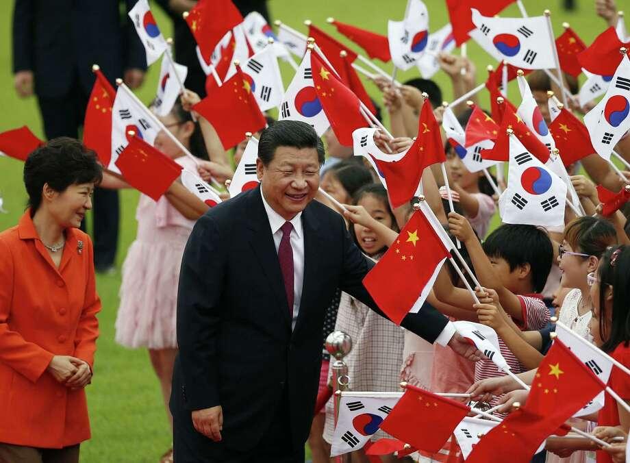Chinese President Xi Jinping and South Korean President Park Geun-hye (left), greeting children in Seoul, unite against North Korean nuclear proliferation. Photo: Kim Hong-Ji / New York Times / POOL