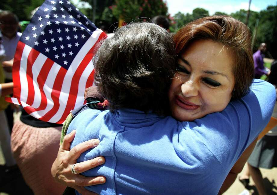 Amanda Castano Gallego, right, gets a hug from co-worker Catherine Hutchison following a naturalization ceremony at the Benjamin L Hooks Central Library in Memphis, Tenn. Thursday, July 3, 2014.  Photo: Mike Brown, Associated Press / The Commercial Appeal