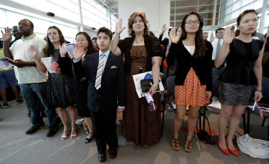 People take the oath of U.S. citizenship during a naturalization ceremony in Irving, Texas, Thursday, July 3, 2014. The Immigration and Naturalization Service is swearing in over 9,000 new citizens over the Fourth of July holiday week in ceremonies held around the country.  Photo: LM Otero, Associated Press / AP