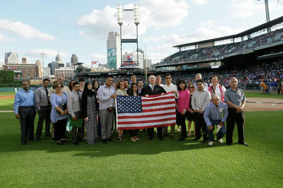 Judge John Corbett O'Meara, center, stands with 33 new U.S. citizens after a pre-game U.S. citizenship and immigration naturalization ceremony before the baseball game between the Detroit Tigers and the Tampa Bay Rays in Detroit, Thursday, July 3, 2014.  Photo: Carlos Osorio, Associated Press / AP