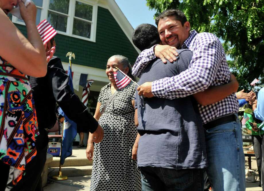 Romario Gonzales hugs his nephew Wilson Gonzales after a naturalization ceremony Thursday, July 3, 2014, at Centennial Village in Greeley, Colo. Wilson was surprised to learn that he too would become a United States citizen because his father completed his naturalization.  Photo: Joshua Polson, Associated Press / The Greeley Tribune