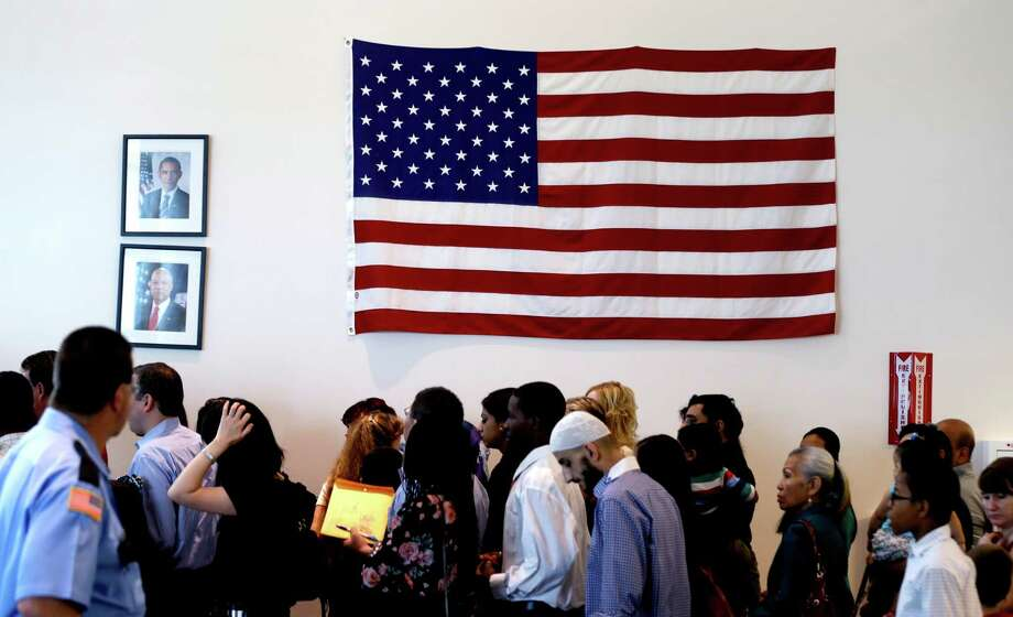 People file past the U.S. flag and a portrait of President Obama on their way to attend a naturalization ceremony in Irving, Texas, Thursday, July 3, 2014.  Photo: LM Otero, Associated Press / AP
