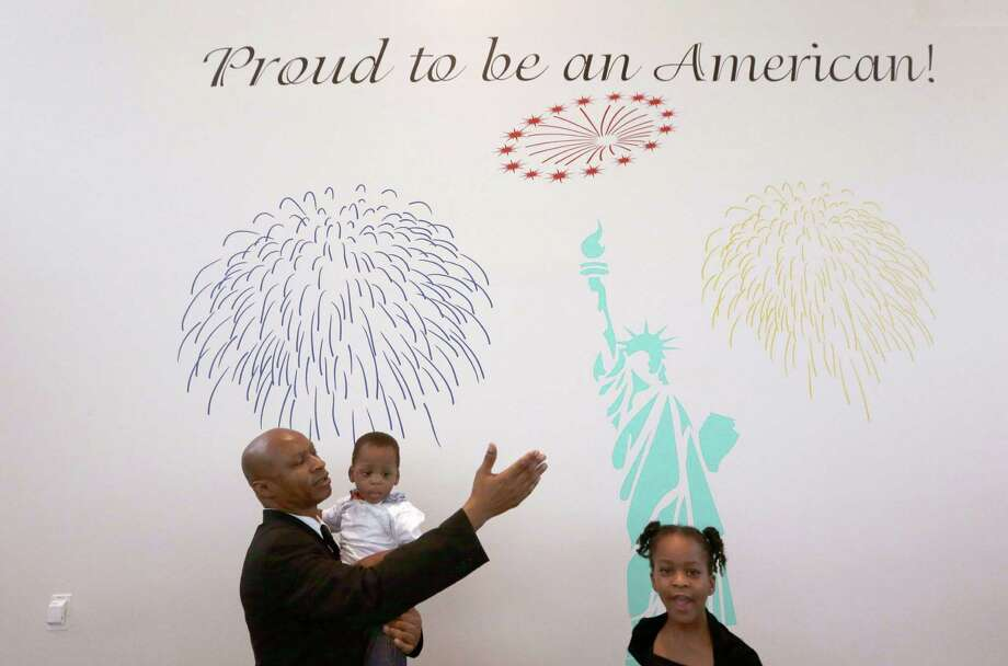 Jacob Udeme, originally from Nigeria, holds his son Davis with daughter Michelle as he calls his friends and family over to take a photo in front of a mural after Udeme became a U.S. citizenship during a naturalization ceremony in Irving, Texas, Thursday, July 3, 2014. Photo: LM Otero, Associated Press / AP