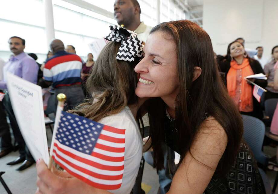 Roberta Minke, right, hugs her daughter Sophia just after taking the oath of U.S. citizenship during a naturalization ceremony in Irving, Texas, Thursday, July 3, 2014.  Photo: LM Otero, Associated Press / AP
