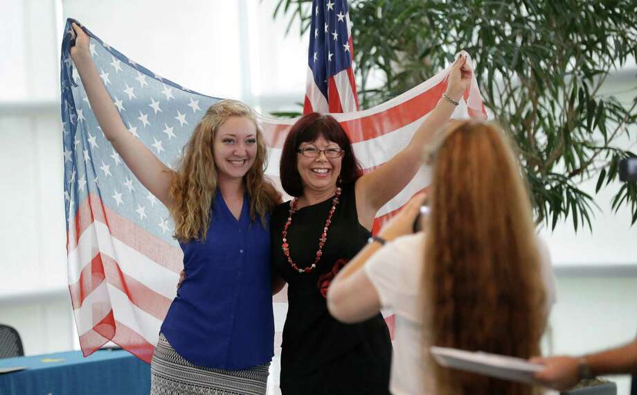 Kari Whittington, left, and Trudie Mare, originally from South Africa, pose for a photo with a U.S. flag after a naturalization ceremony in Irving, Texas, Thursday, July 3, 2014.  Photo: LM Otero, Associated Press / AP
