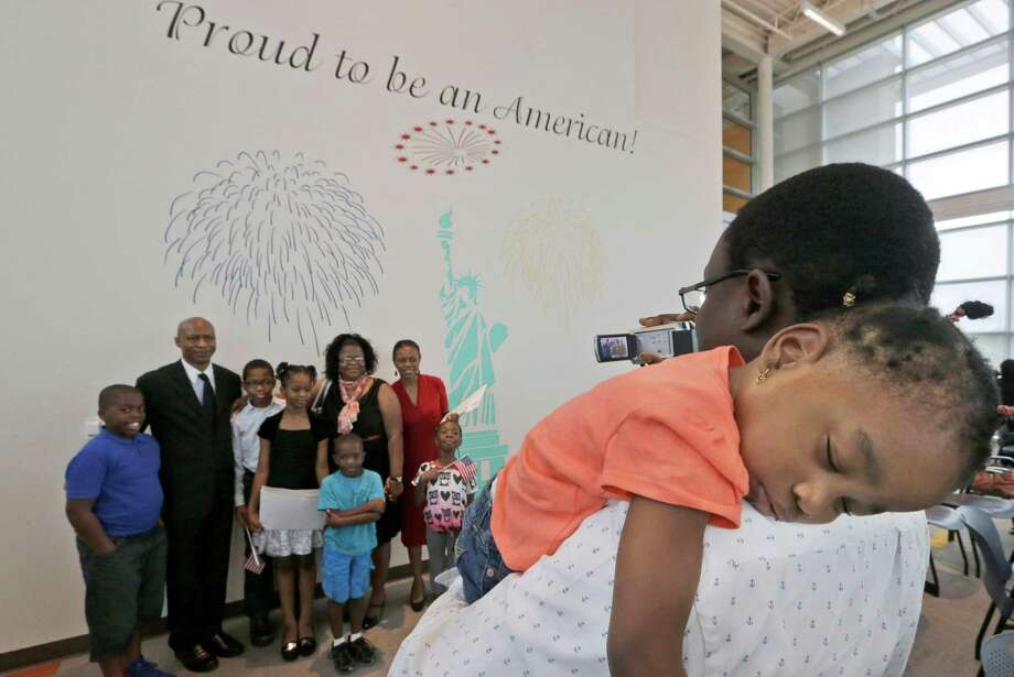 Dammy Oladapo, 3, is held by her father Tosin Oladapo as he makes a photo of his wife, family and friends in front of mural after a naturalization ceremony in Irving, Texas, Thursday, July 3, 2014. Photo: LM Otero, Associated Press / AP