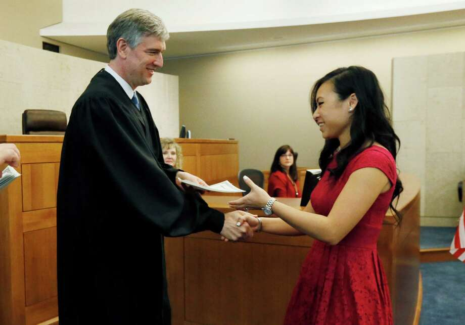 U.S. District Judge Daniel P. Jordan III, left, presents Nikky Phising Phan her certificate of naturalization during a ceremony at the federal courthouse in Jackson, Miss., Thursday, July 3, 2014. Photo: Rogelio V. Solis, Associated Press / AP