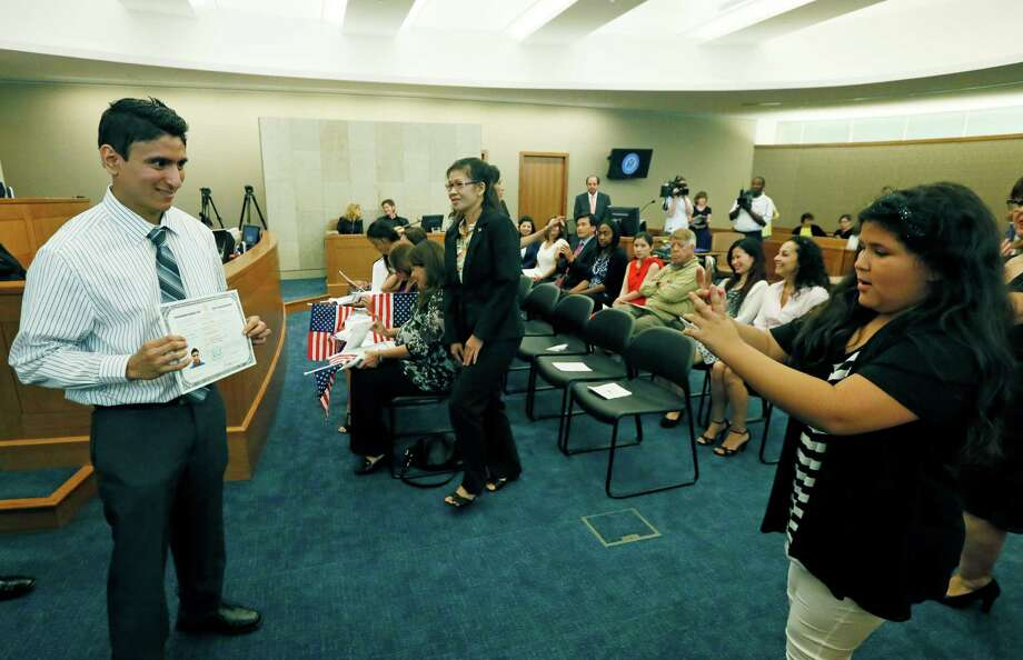 Edwin Scheyner Del Castillo pauses so a family member can take his photograph with his certificate of naturalization during  a naturalization ceremony at the federal courthouse in Jackson, Miss., Thursday, July 3, 2014.  Photo: Rogelio V. Solis, Associated Press / AP