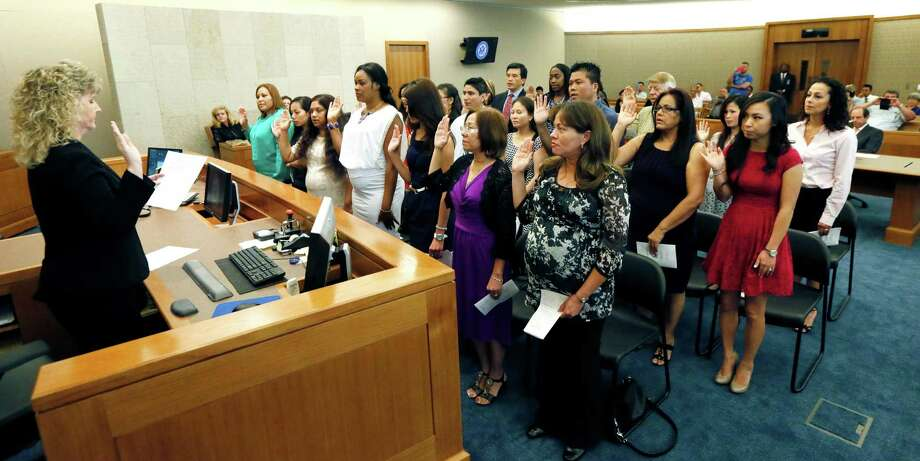Courtroom Deputy Shone Powell, left, leads a group of immigrants in the Oath of Allegiance, Thursday, July 3, 2014 at the federal courthouse in Jackson, Miss.  Photo: Rogelio V. Solis, Associated Press / AP