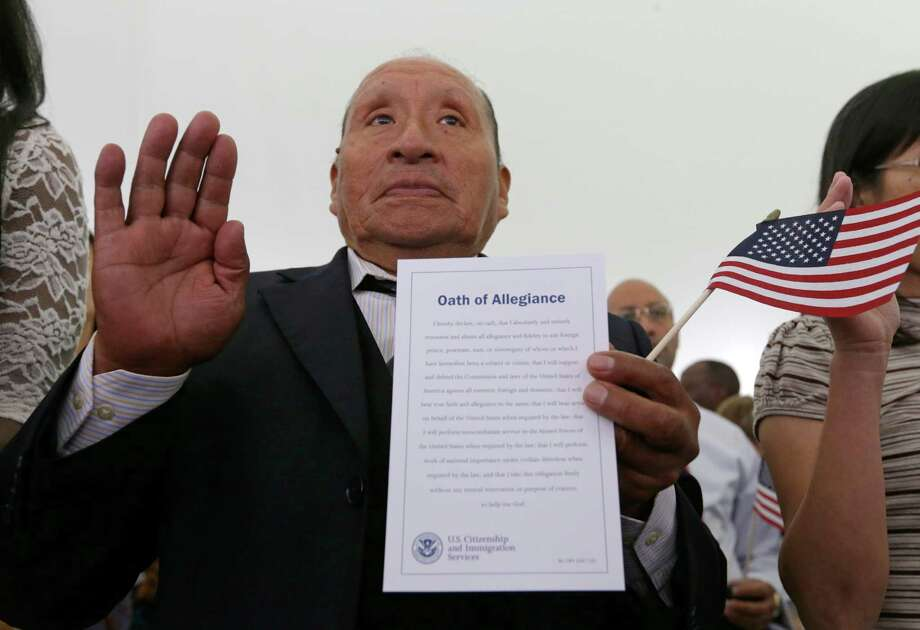 Rodolfo David Miranda, of Peru, takes the Oath of Allegiance at a naturalization ceremony at the Benjamin Harrison Presidential Site in Indianapolis, Thursday, July 3, 2014. Judge Sarah Evans Barker naturalized 101 new citizens at the ceremony.  Photo: Michael Conroy, Associated Press / AP