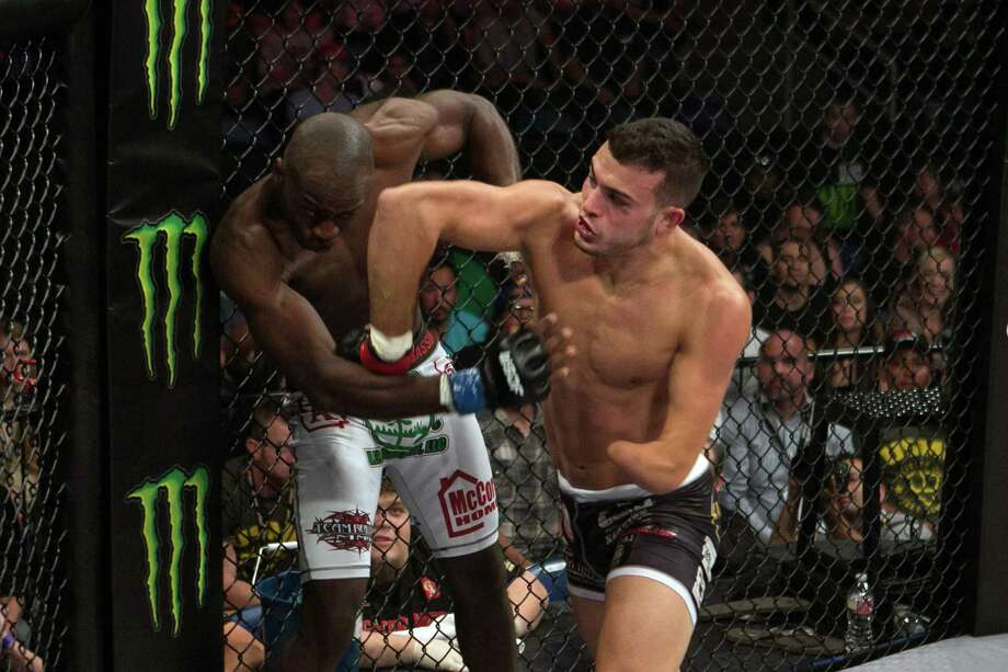 In this Aug. 10, 2013 photo provided by WSOF, Nick Newell, right, battles Keon Caldwell in the World Series of Fighting at Citizens Business Bank Arena in Ontario, Calif. Newell was born with a shortened left arm that ends just below the elbow. He hasn't let that stop him from chasing an MMA career. (AP Photo/WSOF, Lucas Noonan) ORG XMIT: NY157 Photo: Lucas Noonan / World Series of Fighting