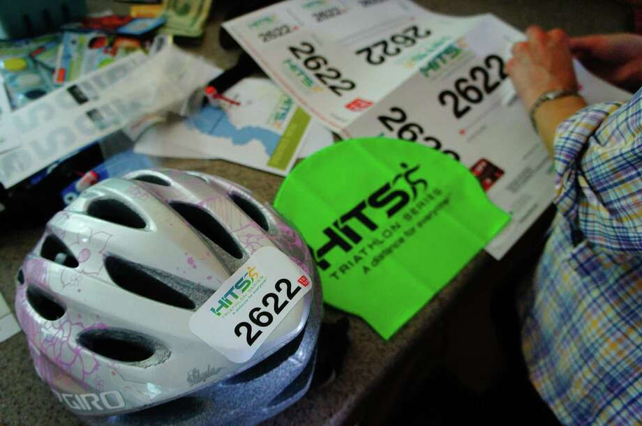 Photo by Herb Terns. Getting ready for HITS North Country triathlon included sticking labels on helmet, swim cap, jersey, bike and more.