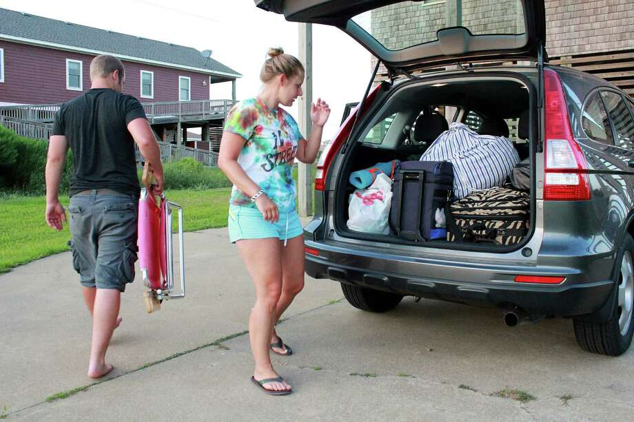 Nicole Specht, and and Ryan Witman, pack their Honda CRV heading back home to Lancaster Pa., before dawn on Thursday, July 3, 2014, during a mandatory evacuation, in Rodanthe, N.C. Arthur strengthened to a hurricane early Thursday and threatened to give North Carolina a glancing blow on Independence Day, prompting a stream of vacationers and residents to head home from some parts of the state's popular but flood-prone Outer Banks. (AP Photo/Jerome Bailey Jr.) ORG XMIT: NCJB101 Photo: Jerome Bailey Jr. / AP