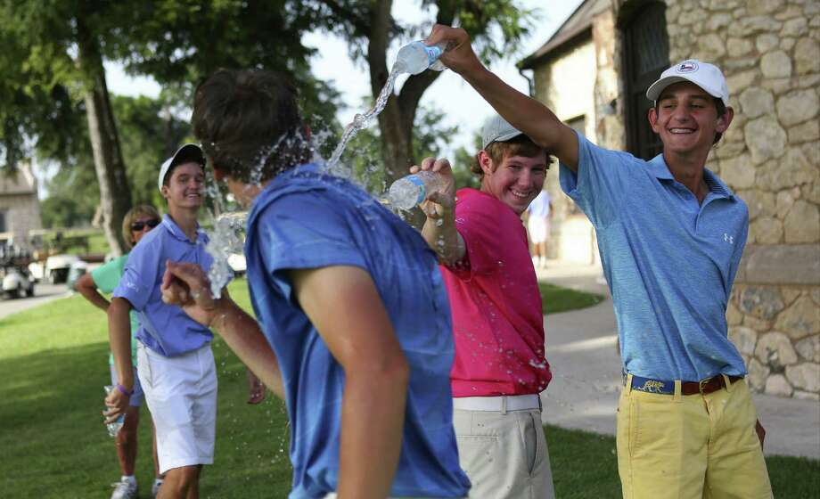Jake Stevenson (second from right) and Mac Meissner pour their water bottles on Reagan graduate Conner Bjugstad after he won the GSA Junior Championship at Brackenridge Park. Photo: Timothy Tai, San Antonio Express-News / © 2014 San Antonio Express-News