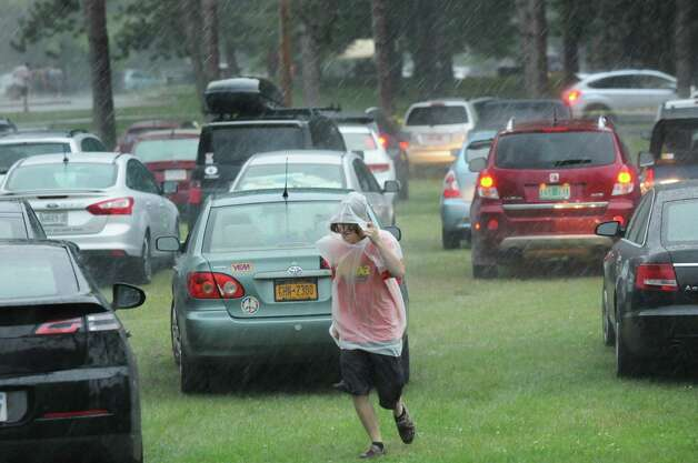 A Phish fan runs between the parked cars during a fast-moving storm on Thursday July 3, 2014, at Saratoga Performing Arts Center in Saratoga Springs, N.Y. (Cindy Schultz / Times Union) Photo: Cindy Schultz