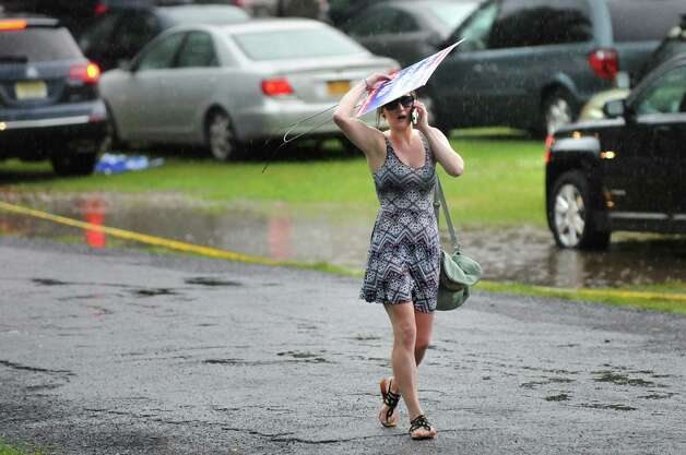 Tara Chmura of Parma Heights, Ohio uses a campaign sign to cover her head after a fast-moving storm moved through the area on Thursday July 3, 2014, at Saratoga Performing Arts Center in Saratoga Springs, N.Y. (Cindy Schultz / Times Union) Photo: Cindy Schultz