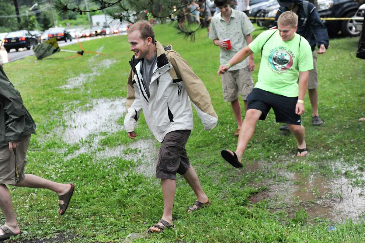 Phish fans navigate the puddles after a fast-moving storm moved through the area on Thursday July 3, 2014, at Saratoga Performing Arts Center in Saratoga Springs, N.Y. (Cindy Schultz / Times Union)