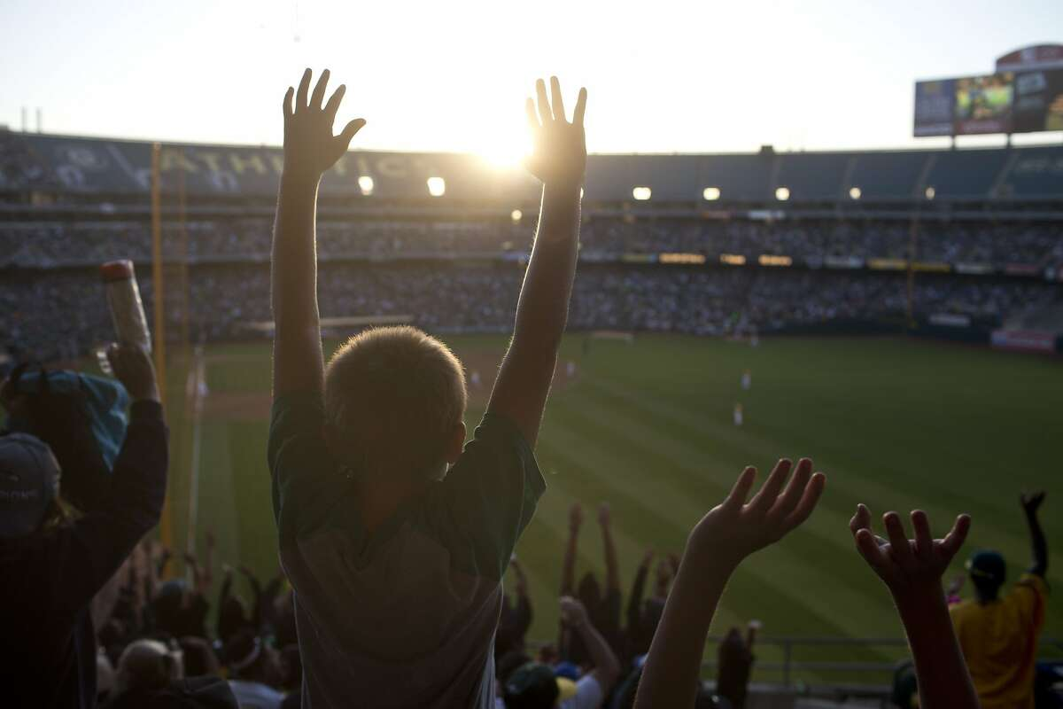 """Zak McCasland 10, takes part in a """"wave"""" during the Oakland Athletics game against the Toronto Blue Jays at the Oakland Coliseum on Thursday, July 3, 2014 in Oakland, Calif."""