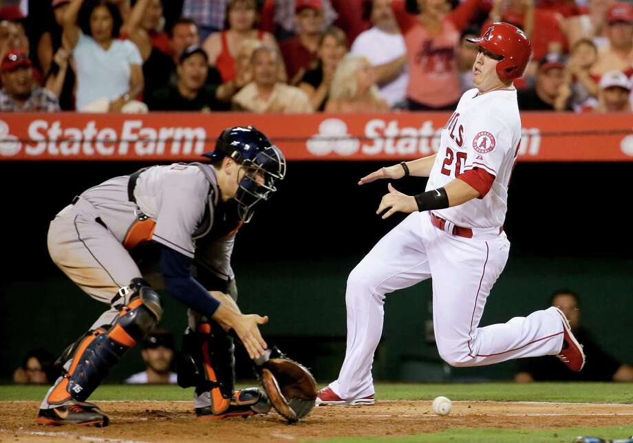 The Angels' C.J. Cron, right, scoots past Astros catcher Jason Castro to score on a double by David Freese, the biggest hit in Los Angeles' four-run fourth inning. Photo: Chris Carlson, STF / AP